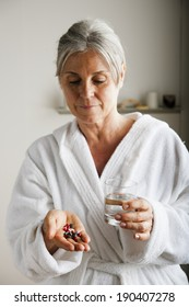 Senior woman holding pills and water in her  hands