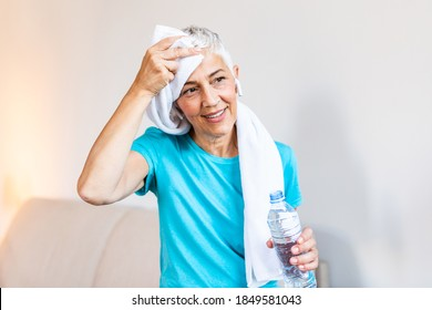 Senior woman holding plastic bottle of water,wiping sweat with a towel, exhausted after the daily training. Elderly woman taking a break while exercising at home.