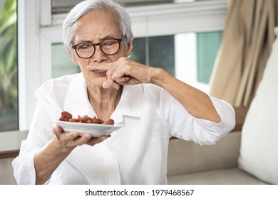 Senior woman holding plate of bad spoiled or expired food in her hand,rotten food,emitting a fetid smell or strong-smelling food,disgusted old elderly cover nose with her finger,diet,nutrition concept