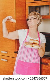 Senior woman is holding plate with heap of donuts in kitchen.