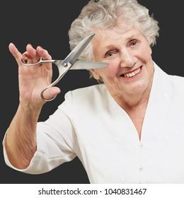 Senior woman holding scissors isolated on black background