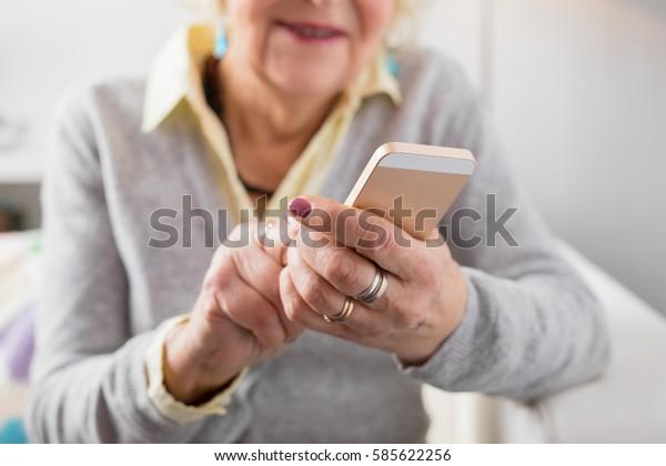 Старший женщина держит смартфон