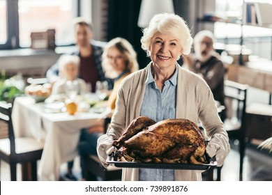 senior woman holding tray with turkey for thanksgiving dinner and blurred family on background