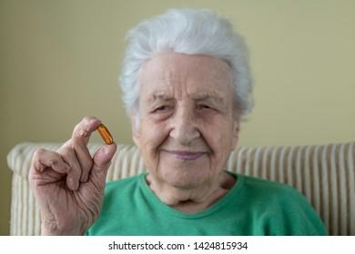 A senior woman holding a vitamin pill