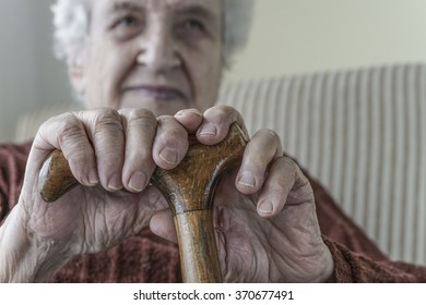 senior woman holding a wooden cane