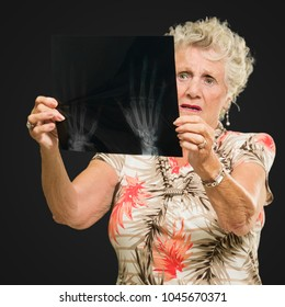 Senior Woman Holding X Ray Report On Black Background