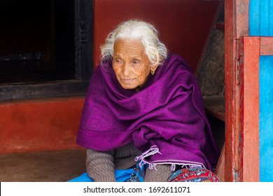 senior woman at home feeling sad. Elderly woman looks sadly outside the Door. Depressed lonely lady standing alone and waiting for come back her Soldier Son at lamjung nepal.  9/23/2019