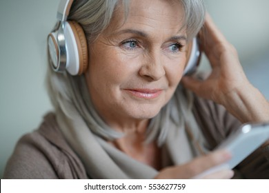 Senior woman at home listening to music with smartphone