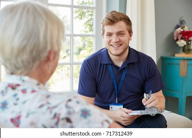 Senior woman at home with male care worker making notes