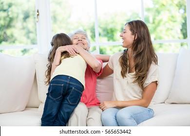 Senior woman hugging granddaughter while sitting on sofa at home