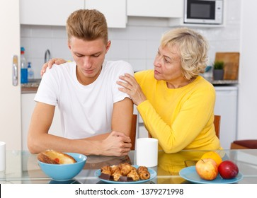 Senior woman hugging and supporting morally her sad adult son at kitchen