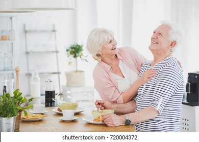 Senior woman hugs husband in striped shirt while sitting in dining room and eating lunch