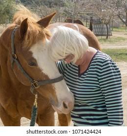 Senior woman hugs a Quarter horse at Aguanga, CA, USA