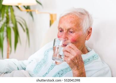Senior woman hydrating herself, drinking fresh water.