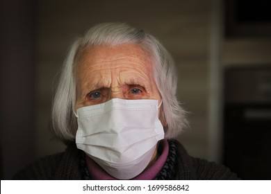 Senior woman with hygienic facial mask. Stay at home. COVID-19 concept.