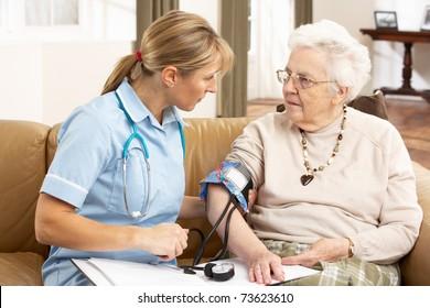 Senior Woman Ihaving Blood Pressure Taken By Health Visitor At Home