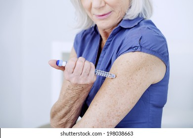 Senior woman injecting herself with insulin.