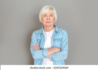 Senior woman in jeans jacket studio isolated on grey wall serious