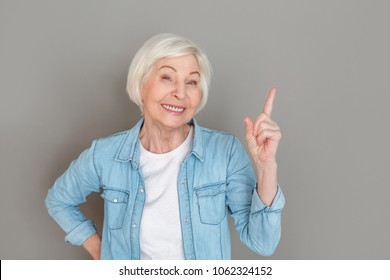 Senior woman in jeans jacket studio isolated on grey wall creative idea