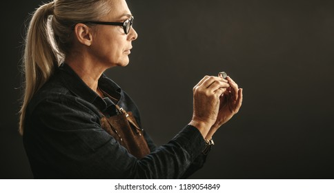 Senior woman jeweler wearing eyeglasses and apron looking at the quality of ring against gray background. Goldsmith examining the ring for flaws.