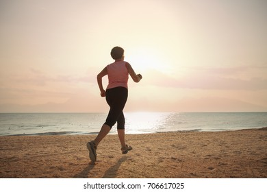 senior woman jogging on sea beach at the sunrise