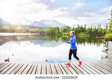 Senior woman jogging round the tarn in beautiful mountains, hills and hotel in background