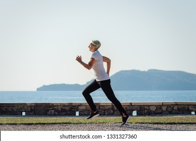 Senior woman jogging at sunrise. Morning running on background the sea and mountains