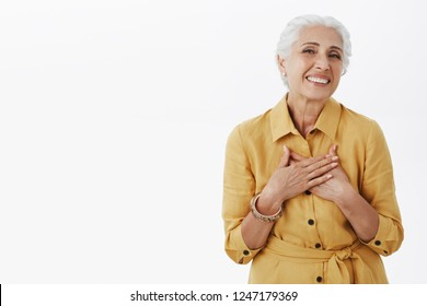 Senior woman keep getting compliments looking fresh and beautiful. Delighted happy charming old lady with white hair in stylish yellow coat holding palms on heart thankfully smiling at camera