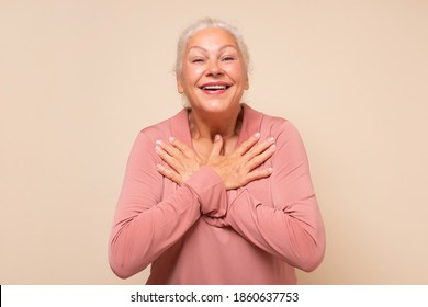 Senior woman keep getting compliments looking fresh. Delighted happy charming old lady with white hair holding palms on heart