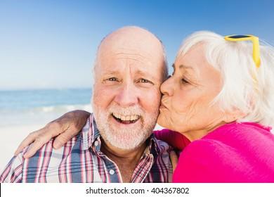 Senior woman kissing husband at the beach