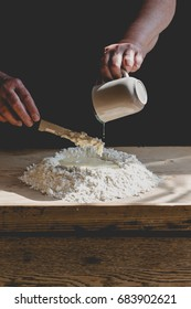 Senior woman kneads pastry, pouring water from mug to flour. Vertical crop, subdued colors, details on old working hands and food ingredients