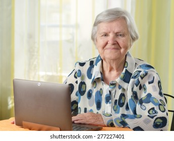 Senior woman with laptop in her room. MANY OTHER PHOTOS FROM THIS SERIES IN MY PORTFOLIO.