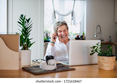 Senior woman with laptop and smartphone working in home office.