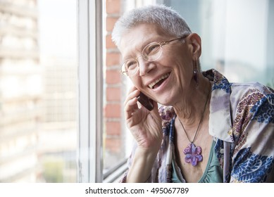 Senior woman laughing cordially over the phone, having a nice humorous talk with a friend or a relative