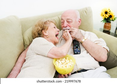 Senior woman laughs and feeds popcorn to her husband as they watch television.