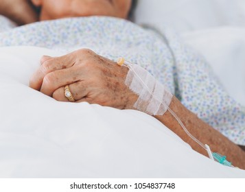 Senior woman laying on bed in hospital room,she's sick.