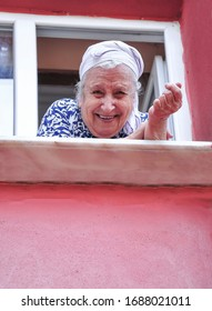 A senior woman leaning on window to looking outside in her apartment