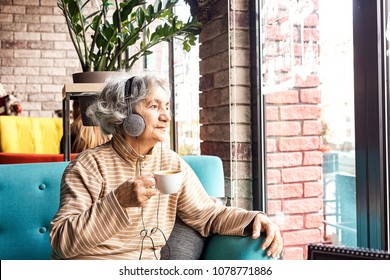 Senior woman listening to music and drinking coffee in restaurant.