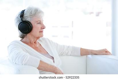 Senior woman listening music with headphones sitting on a sofa