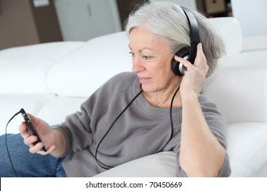 Senior woman listening to music with headphones