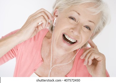 A senior woman listening to music on an mp3 player, laughing