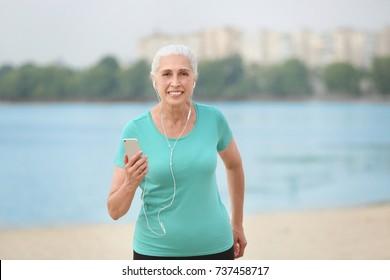 Senior woman listening to music outdoors