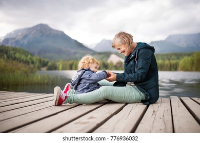 Senior woman with little boy at the lake.