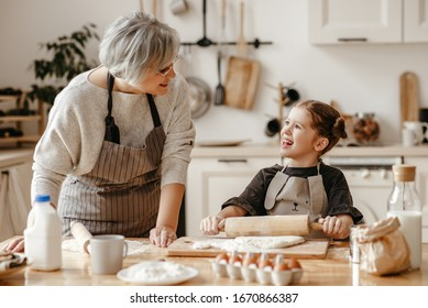 Senior woman and little girl looking at each other while rolling soft dough during pastry preparation in cozy kitchen at home