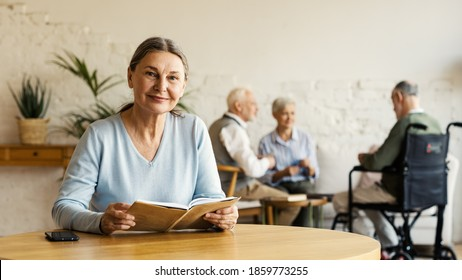 Senior woman looking at camera and smiling while reading book sitting at table in assisted living home. Three elderly people including disabled man in wheelchair playing cards in background