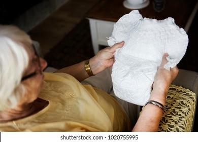 Senior woman looking at a diaper