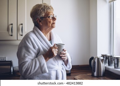 Senior woman looking out of her kitchen window with a cup of tea in hand.