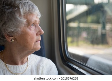 Senior woman looking out of  the window on a train journey