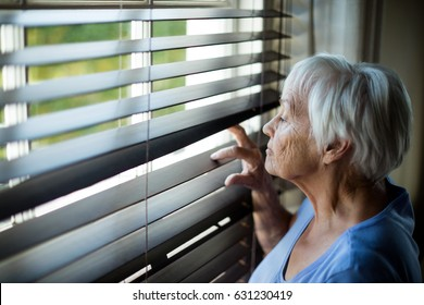 Senior woman looking out from window blind at home