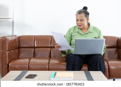senior woman looking paper document and using laptop computer at home